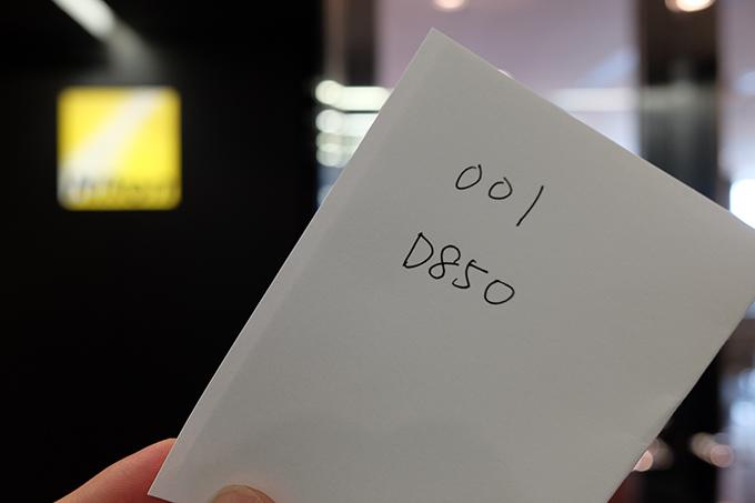 ニコンセンター大阪で配られた整理券。受付カウンターの番号と、本日メンテナンスを受ける機種が書かれている。ほんと手書きのメモ。