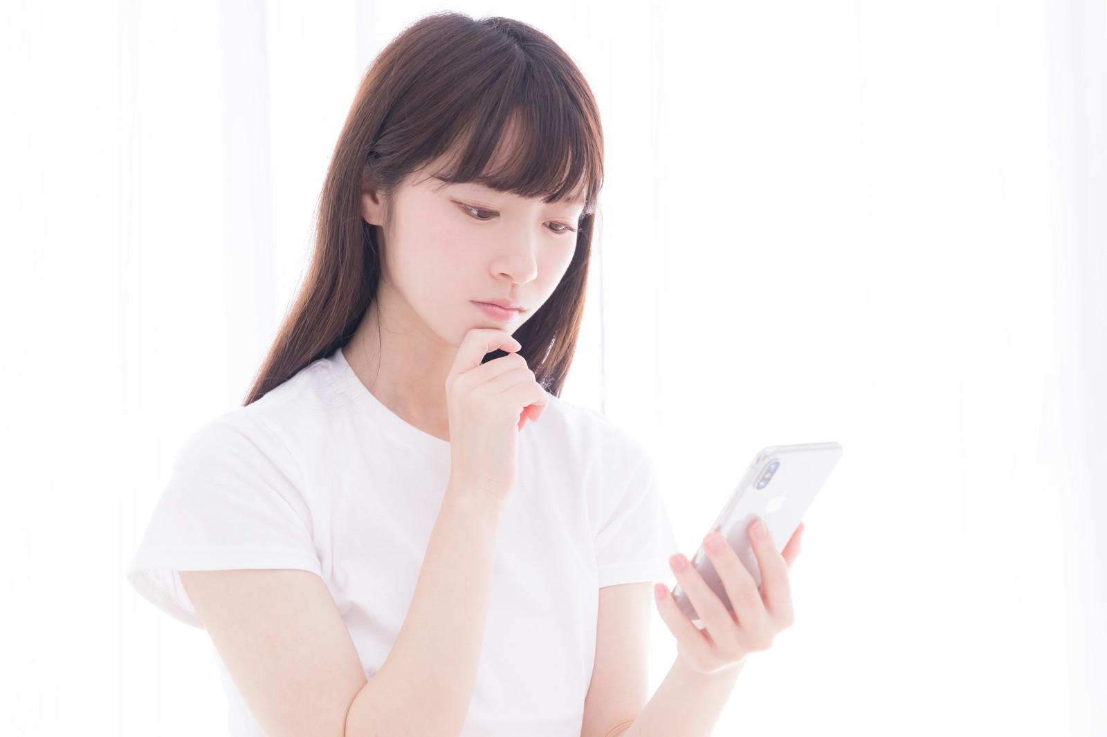 スマホを片手にLINEポイントを貯める方法を考える女性