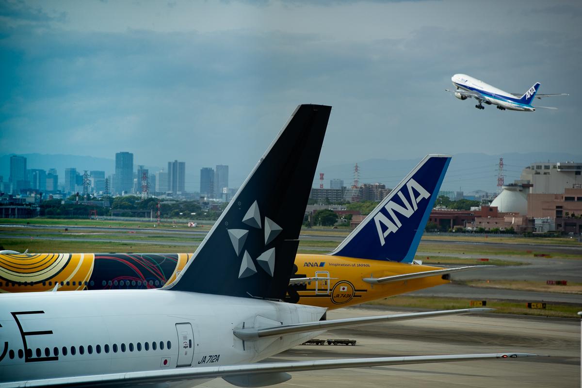 伊丹空港を離陸していく飛行機と特別塗装機