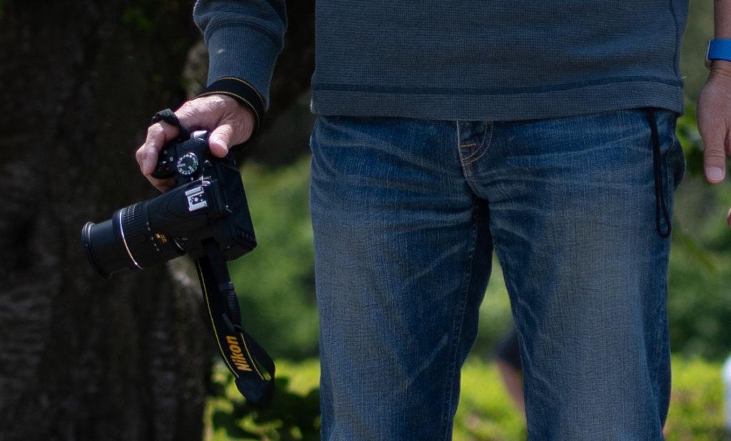 ニコンのカメラを持つルーク・オザワさん。